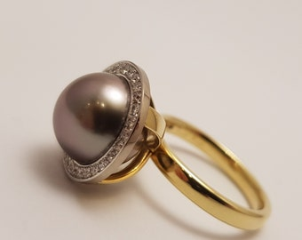 Tahitian pearl in 14k gold ring with diamonds around. Unique style ring made by Cober.