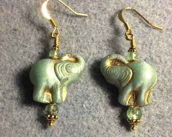 Light green and gold Czech glass elephant bead dangle earrings adorned with light green Czech glass beads.