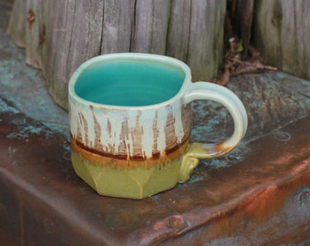 Wheel-thrown mug with a rich blue-brown glaze accented by patina green
