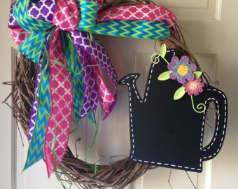 Handwoven grapevine with spring bow and watering can