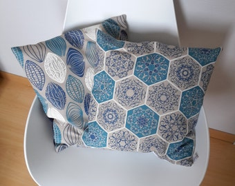 Cushion cover in blue and white geometric patterns on taupe gray background