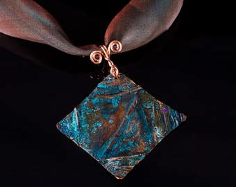 Fold formed copper diamond shaped pendant with blue green and rust patina on hand dyed ribbon