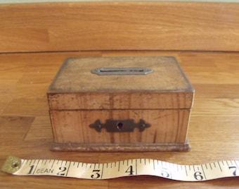 A wooden hand made money box 1950