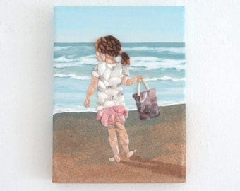 Little Girl on Beach with Bucket in Seashell Mosaic on Sand