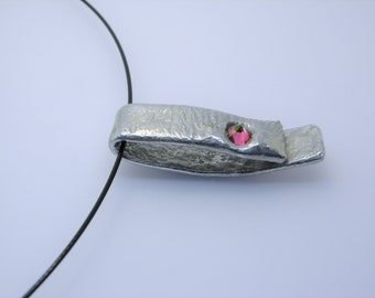 oblong pendant with molten pink cubic zirconia on black wire necklace