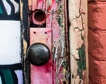 Doorknob, color photograph of a dark brown doorknob surrounded in pinks