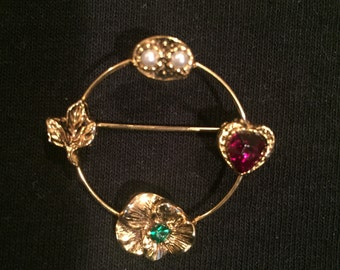 Brooch with open design and a different stone on each side of circle