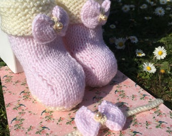 Pink hand knitted baby bootees and matching hairband