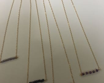 Beaded gemstone necklaces on gold chain.