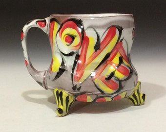Love mug with feet red yellow and black on white