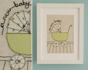 A New Baby framed handmade embroidered applique picture. Traditional pram design with French knot blanket.
