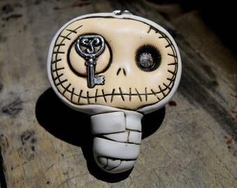 Adorable baby mummy keychain in dirty white. Creepy and cute skull with a celtic key in his eye.
