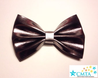 One dark grey faux leather hair bow. Portion of sale goes to charity. Cruelty-free.
