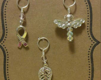 Silver toned knitting stitch marker set of 3. Angel, hope ribbon and filigree leaf.