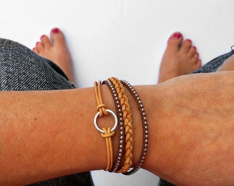 leather braided bracelet in neutral brown tones with lobster clasp chain closure. infinity circle charm.