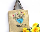 Modern burlap shopping market tote, hand embroidered with a blue abstract flower