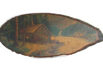 vintage rustic mountain cabin scene on a wood slice
