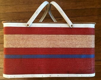 Vintage circa 1960s Redmon Picnic Basket. Red, blue and cream striped woven design. White metal trim and double handles, with dishes