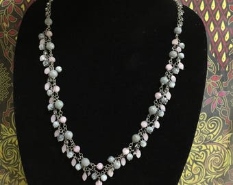 Statement necklace in various shades of grey and pink.