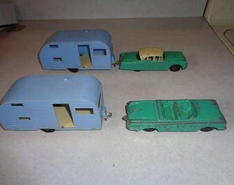 Two 1950s era Tootsietoy cars pulling vintage campers,A Packard and a Oldsmobile