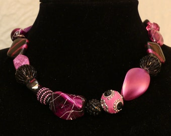 Fun pink and black necklace will draw every eye.