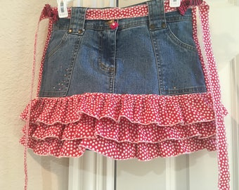 Child Jean Apron with three red polka dot ruffles. Apron is 11-1/2 inches long.