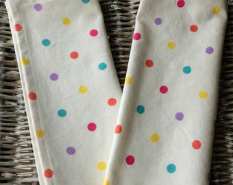 Spotty cotton tea towel in cream fabric with purple, blue, orange and yellow spots
