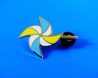 blue and yellow pinwheel enamel pin