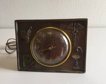 vintage/antique metal clock with medical/pharmacy/alchemy symbols