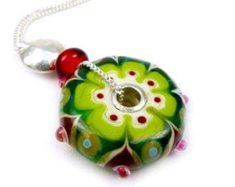 Green, garnet lampwork glass donut pendant on silver chain