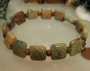 Sea sediment jasper stretch bracelet with copper disc charm.