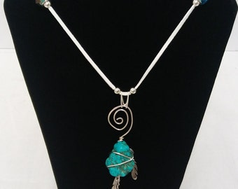 Wire wrapped Howlite (Turquoise) stone with feathers.