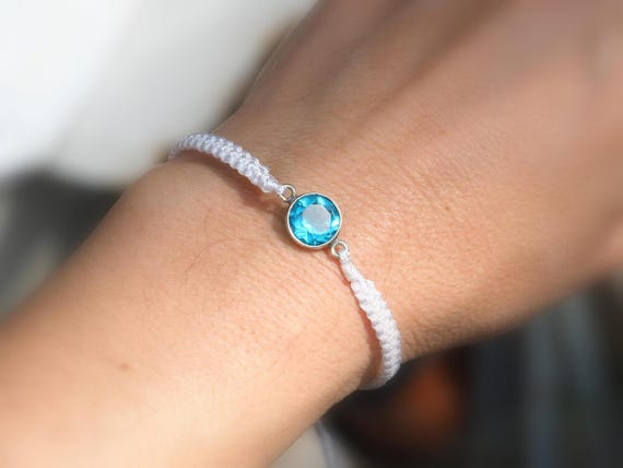 White string bracelet with blue crystal