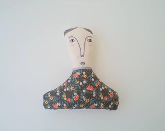 Art doll wearing tiny flowers
