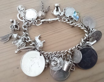 Vintage sterling silver charm bracelet with 29 coins and charms