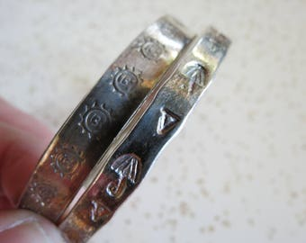 Pair of Vintage Taxco Mexican Silver Bangle Bracelets Pressed with Suns and Umbrellas Eagle Mark