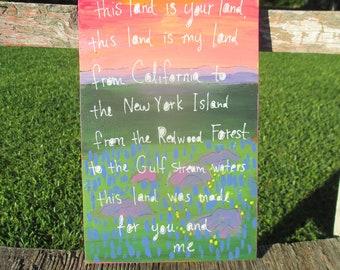 woody guthrie lyrics painting on salvaged wood, this land is your land, American art, landscape painting, folk song lyrics, folk art