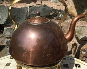 Antique brass andcopper kettle with a brass trivet