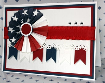 Patriotic rosette greeting card in red, white and blue embellished with ribbon and punched paper.