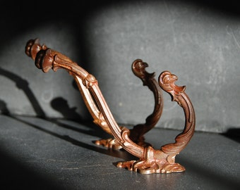 2 vintage cast iron coat,  hat hooks. Identical, eagle heads on bottom hook and flower on top. Good vintage condition,early 20th Century.
