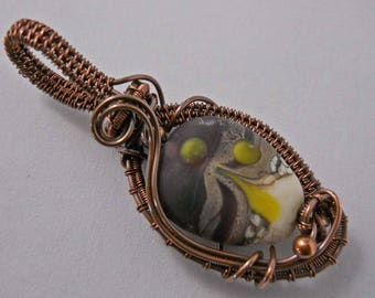 etched white and transparent purple lampwork bead with yellow dots wrapped in oxidized copper wire pendant