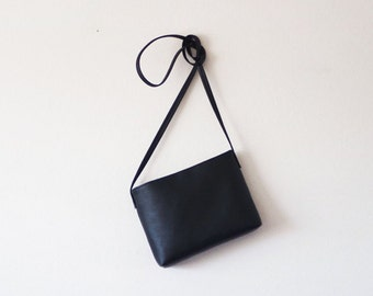 Minimalist black leather crossbody bag with magnetic closure