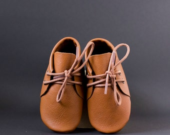 Brown baby moccasins with shoelaces