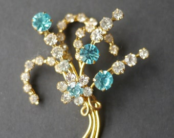 Rhinestone floral spray vintage brooch, blue and clear stones on gold tone wire