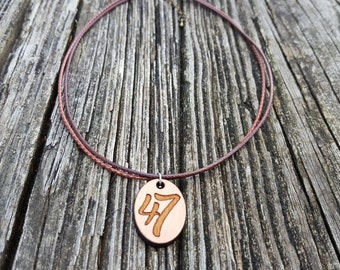 Leather cord and wooden pendant necklace to celebrate Down Syndrome and 47 chromosomes.