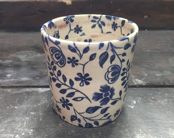 Cup turned stoneware oxides under enamel decoration.