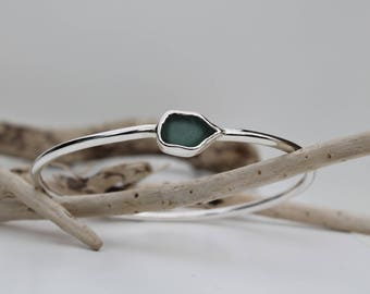 Silver bangle with a teal green sea glass setting