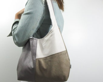 leather hobo bag in color block fashion. large shoulder purse in faux leather silver, gold, and off white. metallic purse.