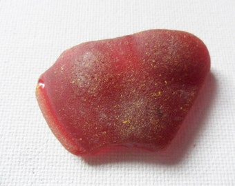 Large curved red sea glass found on the East coast of england