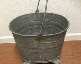 Vintage galvanized bucket on wheels